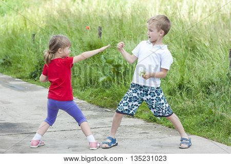 Children playing fighting on sunny summer day