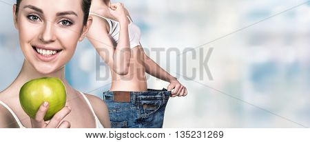 Young slim woman holding an apple and wearing oversize jeans over blurred background