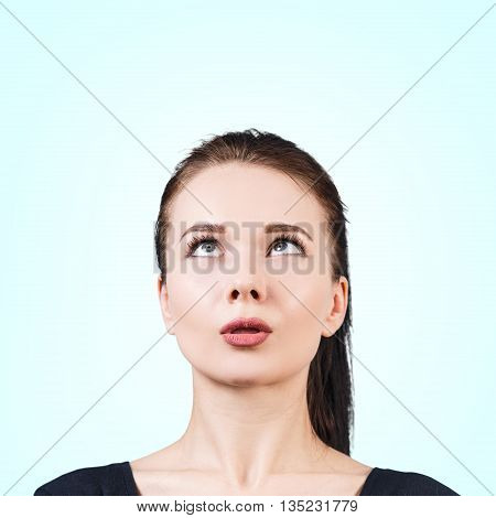 Thinking young woman looking up with funny face over blue background