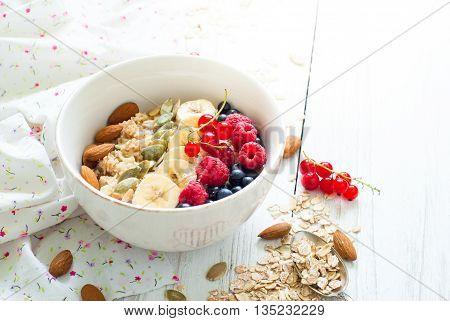 Healthy breakfast. Oatmeal porridge banana raspberries blueberries red currants pumpkin seeds and almonds in a bowl on white background.
