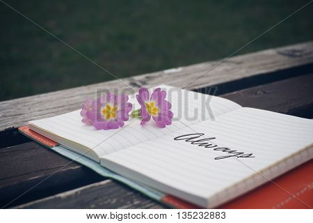 Alway text on open notebook with flower on wooden table