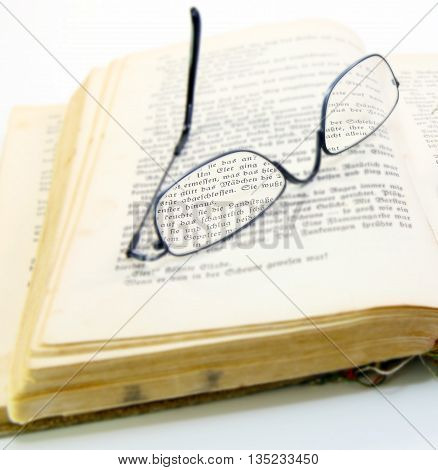 an old open book with broken glasses