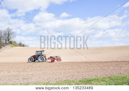 Tractor Compresses The Soil After Planting With Rollers.