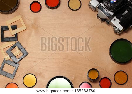 colored photo filters camera and slides on wooden background