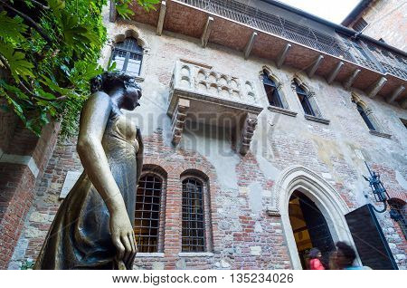 VERONA, ITALY - SEP 5, 2015: Statue of Juliet with balcony in the background. Verona, Italy.