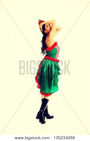 Woman wearing elf clothes holding her head