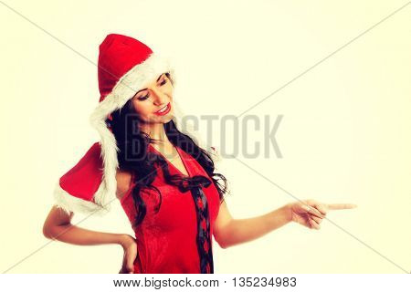 Woman wearing santa clothes, pointing left