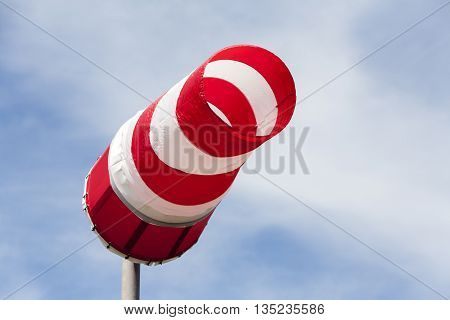 Wind is blowing through a red and white windsock
