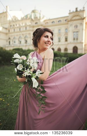 Beautiful bride, girl outdoors posing with bouquet.
