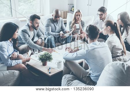 Discussing strategy. Group of confident business people discussing something while sitting around the desk together and pointing large paper laying on it
