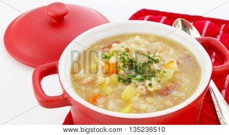 Barley soup in a red pot with lid and spoon