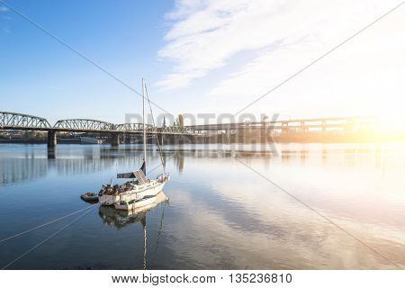 sail boat on tranquil water with steel bridge at sunrise