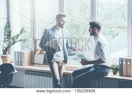 Asking for professional advice. Two young businessmen in smart casual wear talking and gesturing while leaning at the window sill in office