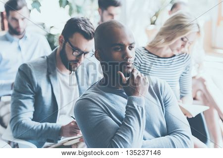 Overthinking info. Handsome African man holding hand on chin and looking thoughtful while sitting on conference with other people