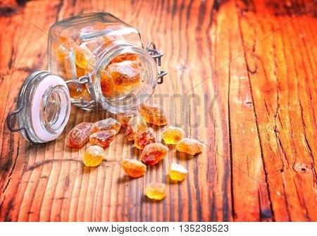 preserving jar with sugar candy on a old wooden table
