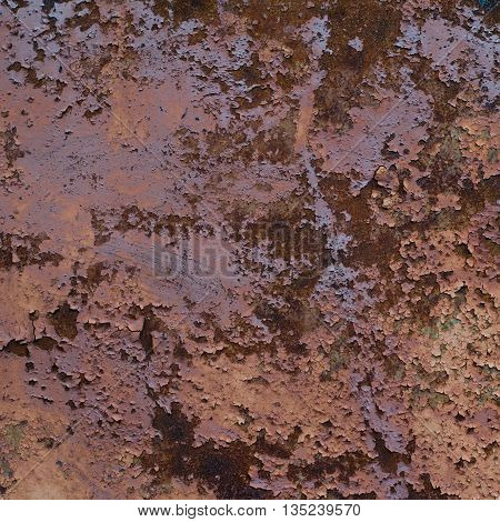 Vintage iron wall painted in brown and purple with many layers of paint with cracks and rust