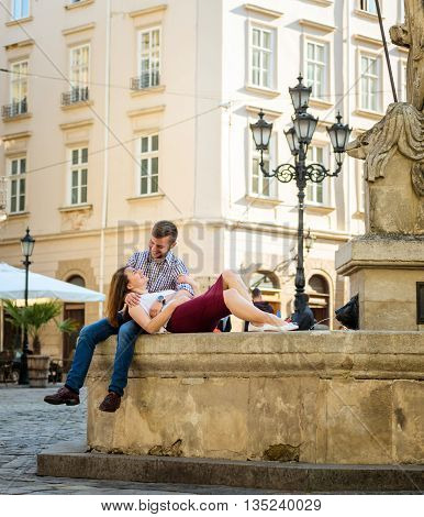 Pretty Young Girlfriend Lying on the Lap of his Handsome Boyfriend While Relaxing at the fountain