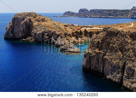 Bay among rocks Greece Rhodes Lindos sunny day view from the sea