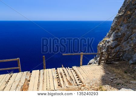 view from cliff on brusochny broken bridge and sea summer sun Lindos