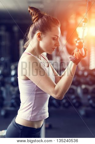 Young Woman Doing Pushdown On Cable Machine In Gym