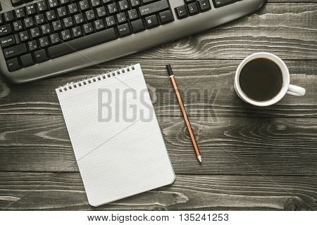 Office desk with notepad pencil keyboard and cup of coffee bussiness concept