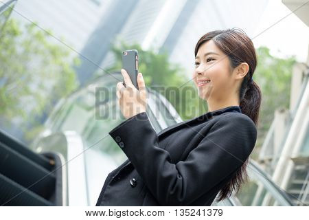Businesswoman standing on escalator and looking at mobile phone