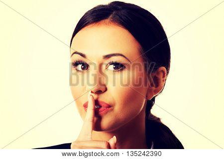Businesswoman making silent sign