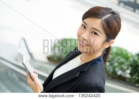 Young Businesswoman standing on escalator