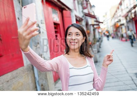 Woman taking self image by cellphone in Macau