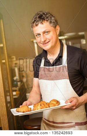 baker concept. baker concept. Happy baker showing plate of fresh croissant in the kitchen of the bakery