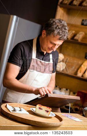 baker concept. baker produces customer payment for dessert, focus on desert