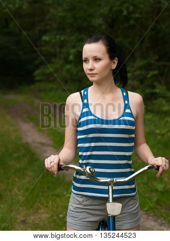 young girl on bike in woods brunette in the striped shirt in the background of the forest