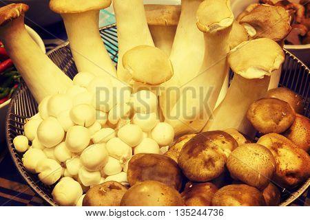 King oyster mushroom and shimeji mushroom and Shitake mushroom on metal basket warm tone
