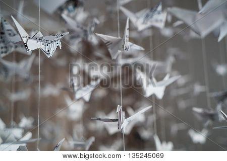 swarm of origami cranes made of music manuscript paper