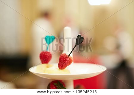 Strawberry on a white plate on cocktail