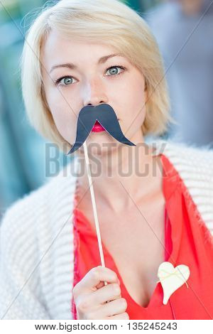 Portrait of girl wearing fake mustache: symbol of Movember, annual, month-long event involving the growing of moustaches during the month of November to raise awareness of men's health issues.