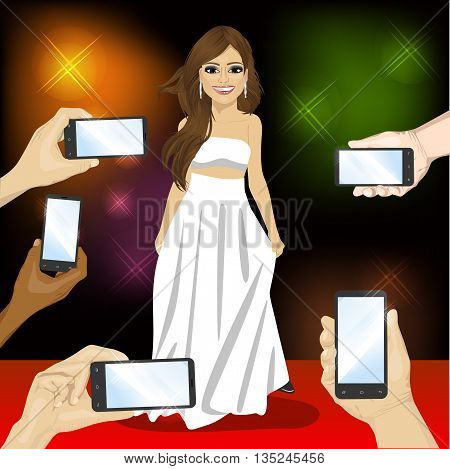 Beautiful famous woman posing on a red carpet for people with smartphones