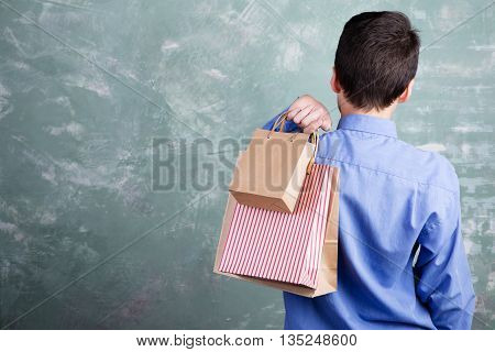 Teen Boy Standing Back And Holding Shopping Package
