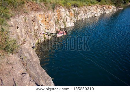 Active man with outstretched hands dives off a cliff. Sunny day on the coast.