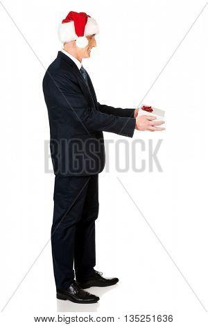 Full length man wearing santa hat holding gift