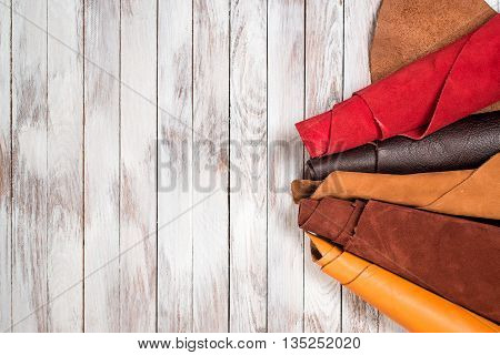 Brightly colored leather in rolls on the white wooden background. Leather craft. Copy space. Top view.