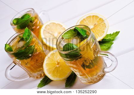Cold tea with ice lemon and mint on a wooden background. Selective focus.