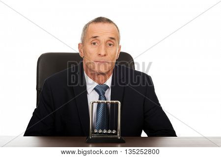 Businessman in the office with newton balls