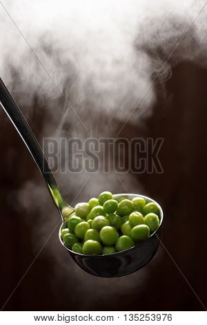 Boiled green peas in a ladle with steam