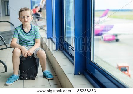 Child Sitting At Bag At The Airport