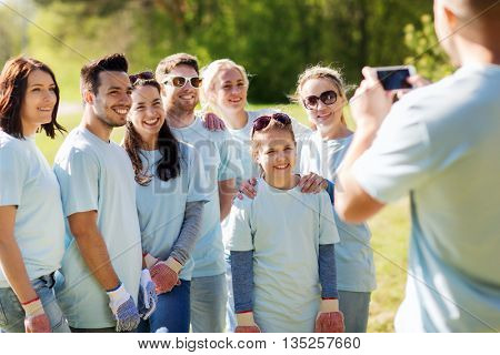 volunteering, charity, people, teamwork and environment concept - group of happy volunteers taking picture by smartphone in park