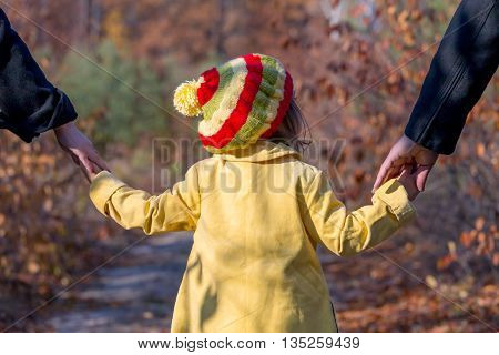 Two Generation Family Walking in Autumnal Forest Father Mother Holding Hands of Little Baby Girl Bright Yellow Clothing Coat and Cap Rear View