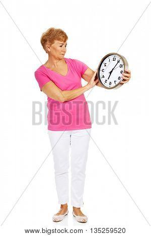Worried senior woman holding big clock