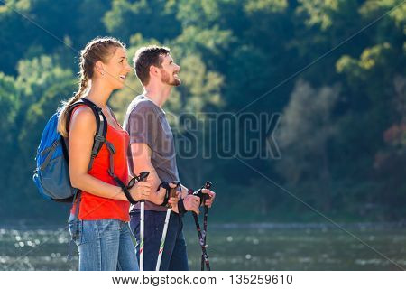 Couple hiking or Nordic walking at river in summer for better fitness