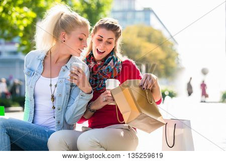 Two women friends sitting on fountain rim in city with shopping bags
